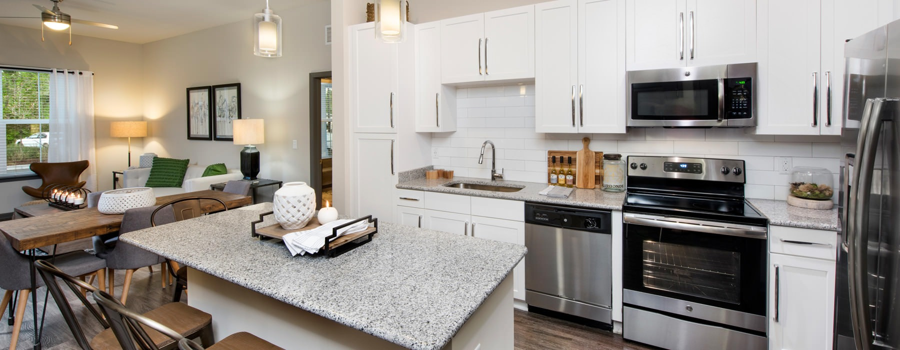 Kitchen with white cabinets, quartz countertops, and pendant lights